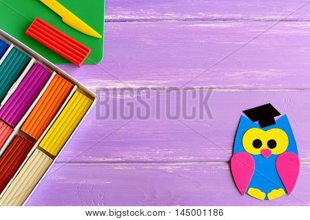 Bright paper owl, colorful plasticine set, plastic board and knife on wooden background with blank space for text. Children education. Back to school background for children