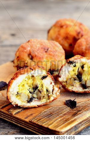 Roasted meatballs stuffed with grated cheese and fried mushrooms. Stuffed meat patties on a cutting board and on wooden background. Homemade cuisine recipe. Closeup