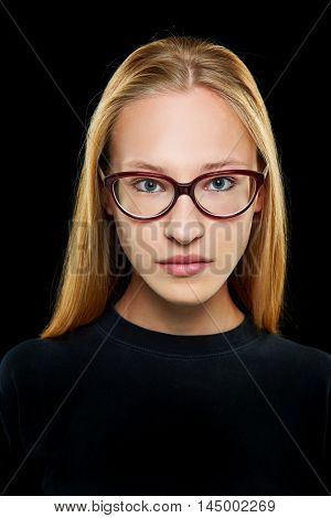 Front view of young blonde woman with nerd glasses looking seriously