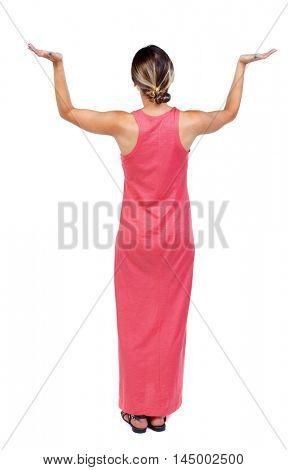 back view of dancing young beautiful woman. girl watching. A slender woman in a long red dress is holding something in her arms.