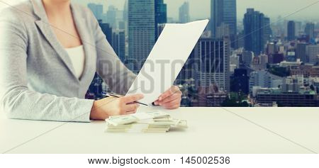 business, finance, tax and people concept - close up of woman hands with us dollar money and tax report paper form over city background