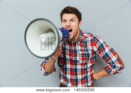 Furious aggressive young man in checkered shirt standing and shouting with loudspeaker over grey background