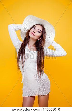 Studio portrait of attractive brunette woman in white dress over bikini and sundown hat on yellow background. Isolate.