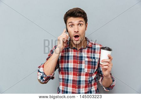 Amazed young man holding takeaway coffee and talking on mobile phone over grey background