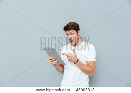 Surprised young man holding and pointing on tablet over grey background