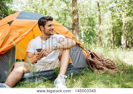 Happy young man tourist sitting in touristic tent and using cell phone in forest
