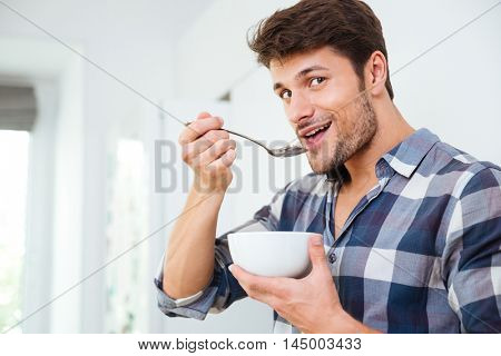 Smiling young man in checkered shirt eating cereals with milk for breakfast on the kitchen