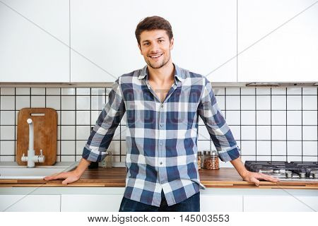 Cheerful young man in checkered shirt standing on the kitchen
