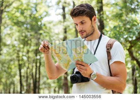 Concentrated young man with modern photo camera standing and using map in forest