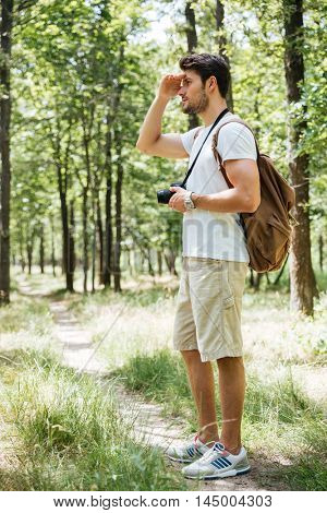Full length of man photographer using modern photo camera and looking far away in forest