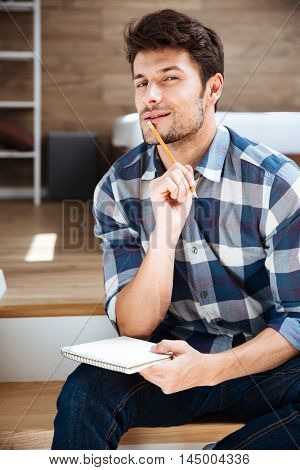 Thoughtful young man in checkered shirt with notepad and pencil sitting and thinking at home