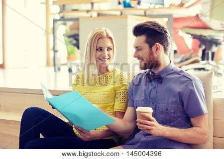 business, startup and  people and concept - happy man and woman with folder  drinking coffee and talking in office