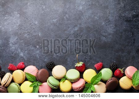 Colorful macaroons and berries on stone table. Sweet macarons with strawberry, raspberry and blackberry. Top view with copy space
