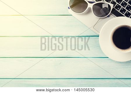 Desk table with laptop, coffee and sunglasses on wooden table with sun beam. Workplace. Top view with copy space.
