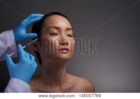 Chinese young woman having painful injections of hyaluronic acid