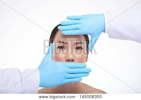 Hands of cosmetologist in front of face of Chinese woman
