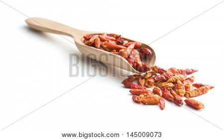 Dried mini chili peppers in wooden scoop. Isolated on white background.