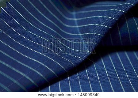 close up dark blue fabric of suit photoshoot by depth of field for object