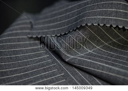 close up dark gray fabric of suit photoshoot by depth of field for object