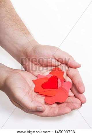 Glass Heart Above Paper Hearts On Male Palms