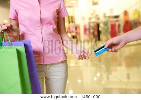 Close-up of woman taking plastic card from male hand in the mall