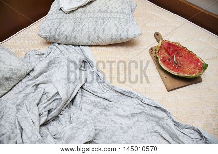 Abandoned for a while bed with watermelon and cigarette but leftovers, sheets scattered.