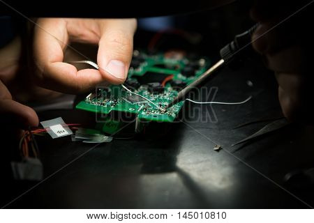 An engineer is welding electronic components on a motherboard