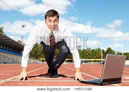 Image of handsome businessman getting ready for race at stadium