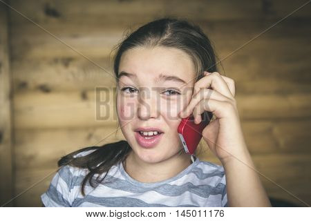 Little teen girl calling by phone.