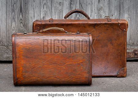 Two old suitcases standing near the garage
