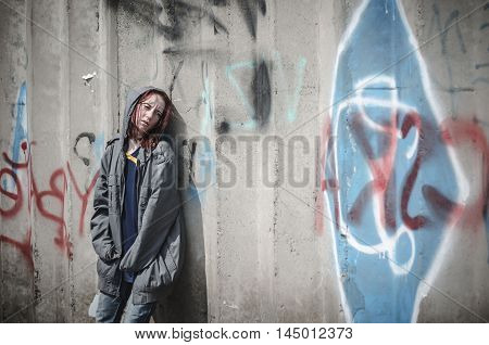 young girl in old dirty ragged clothes standing near the wall. A homeless teenager.