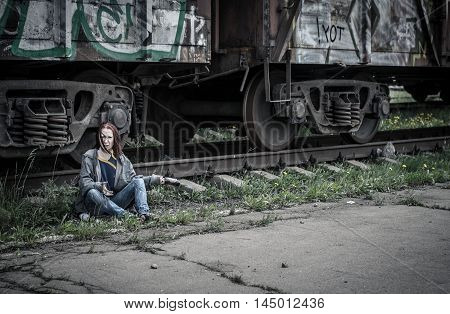 homeless woman in old, torn, dirty clothes, sitting on the ground next to the train on the railway svagonom and aggressive swings on someone an empty glass bottle