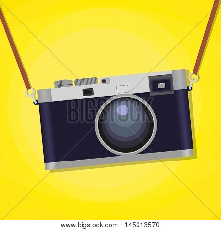 Old photographic camera isolated over yellow background