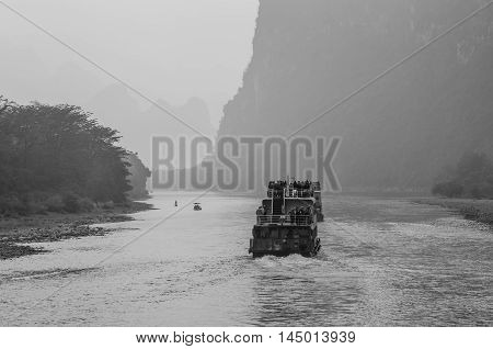Xingping China - October 20 2013: A tourist boats packed with tourists travels the magnificent scenic route along the Li river from Guilin to Yangshou in the haze. Black and white.