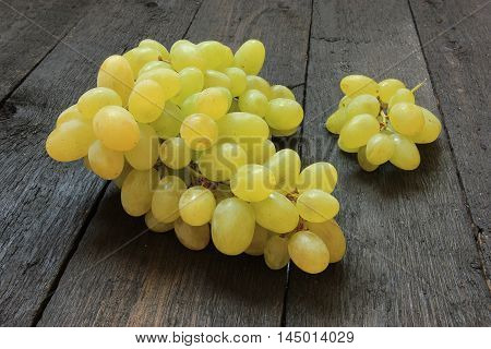 Fresh grapes on wooden background. Close up view of ripe green wine grape. View with fresh green grape.