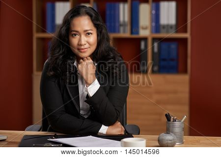 Portrait of smiling Indonesian business lady at her table