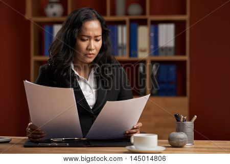 Indonesian female business executive working with papers in office