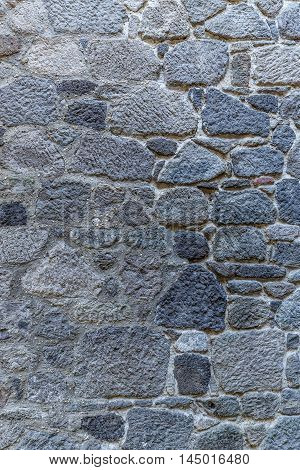 Uneven cracked real stone wall surface, close up