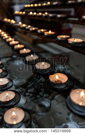 Many candles burning at temple interior, close up