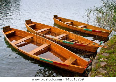 Three wooden rowing boat near the shore
