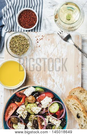 Greek salad with olive oil, bread, oregano, pepper and glass of white wine over old white painted wooden board, top view, copy space, verticall composition