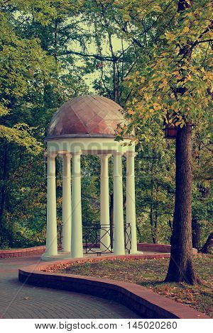 White is an old gazebo in autumn city park