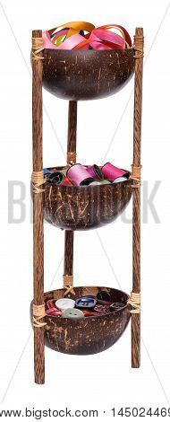 Three tier bowl with colored ribbon, thread and buttons. Made from coconut and wood isolated on white background.