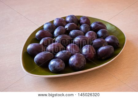 Plums on the plate on the table.