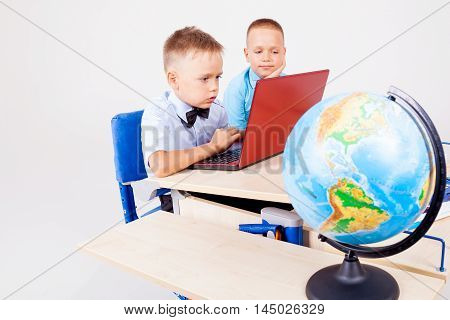 two boys sitting at the computer school globe