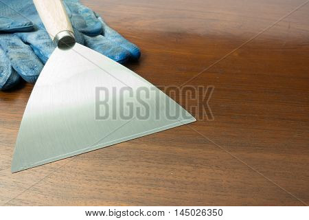 paint scraper with wood handle and working gloves.