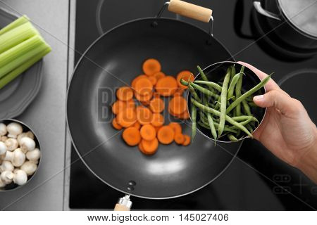 Male hand putting vegetables into pan, top view