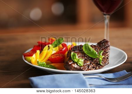 Gourmet steak with vegetables on wooden table