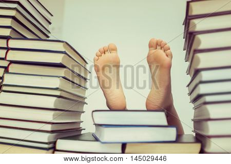 Kid feet with a lot of books