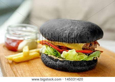 Tasty black burger with french fries and sauce on wooden cutting board